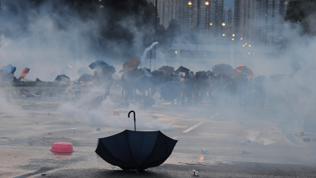 Demonstranten in Hongkong gehen vor Tränengas in Deckung © AP Photo/Kin Cheung
